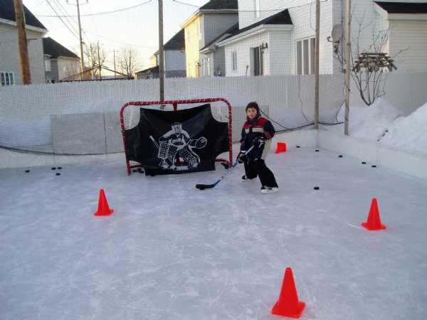 My son and friend playing backyard hockey on my backyard ice rink.