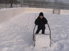 Pushing a lawn roller to pack snow.