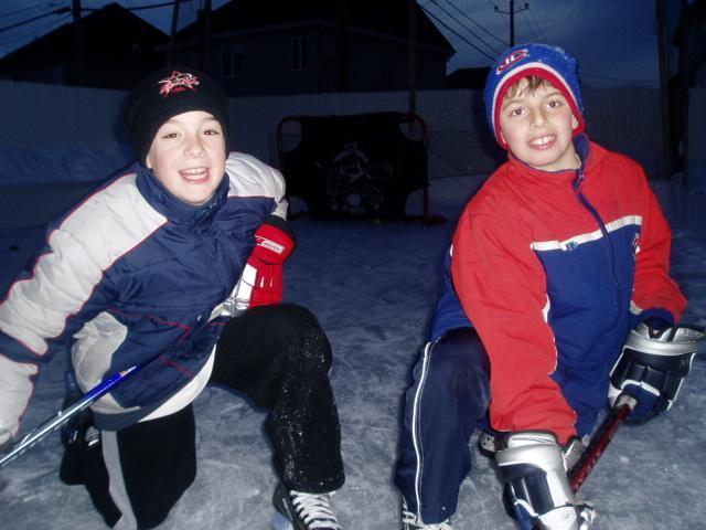 My son and friend playing backyard hockey on my first backyard ice rink.
