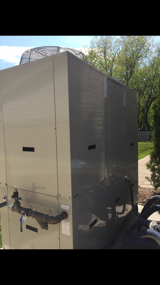 Side view of an ice rink chiller for a  for a residential portable refrigerated outdoor ice hockey rink